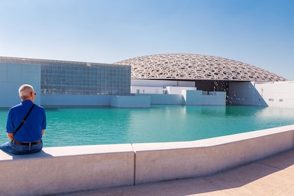 Man sits outside of the Louvre Abu Dhabi