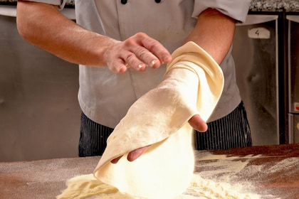 Medium shot of man creating pizza dough