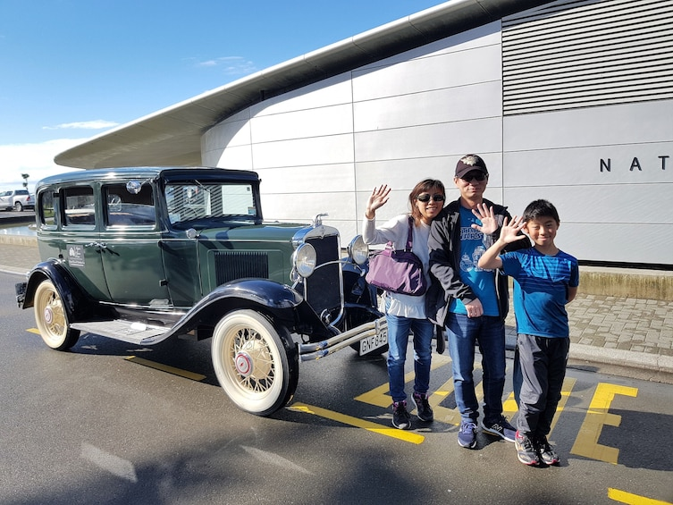 Show item 3 of 8. Family wave as they stand in front of a vintage car in Napier