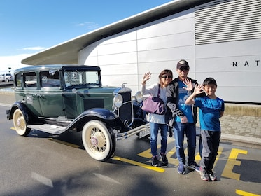 Family wave as they stand in front of a vintage car in Napier