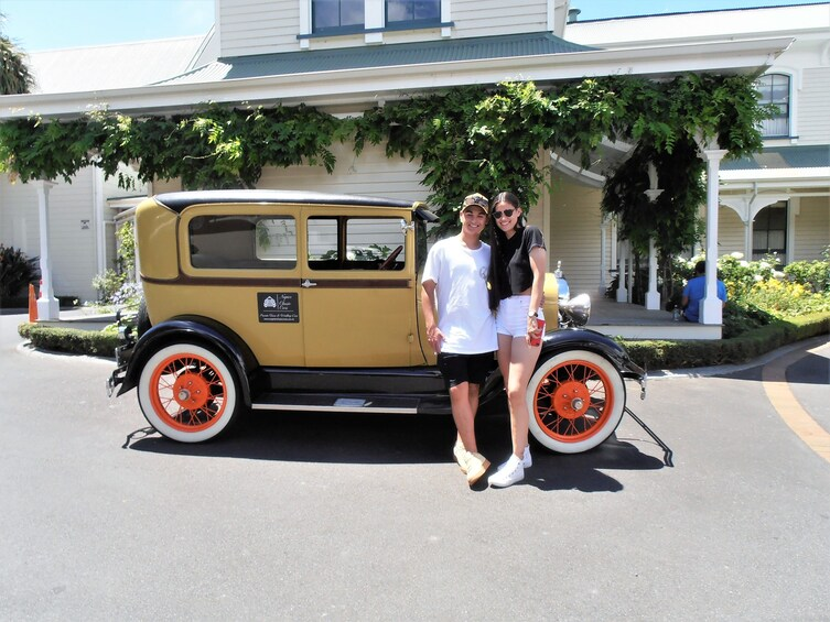 Show item 2 of 8. Couple standing in front of a vintage car in Napier