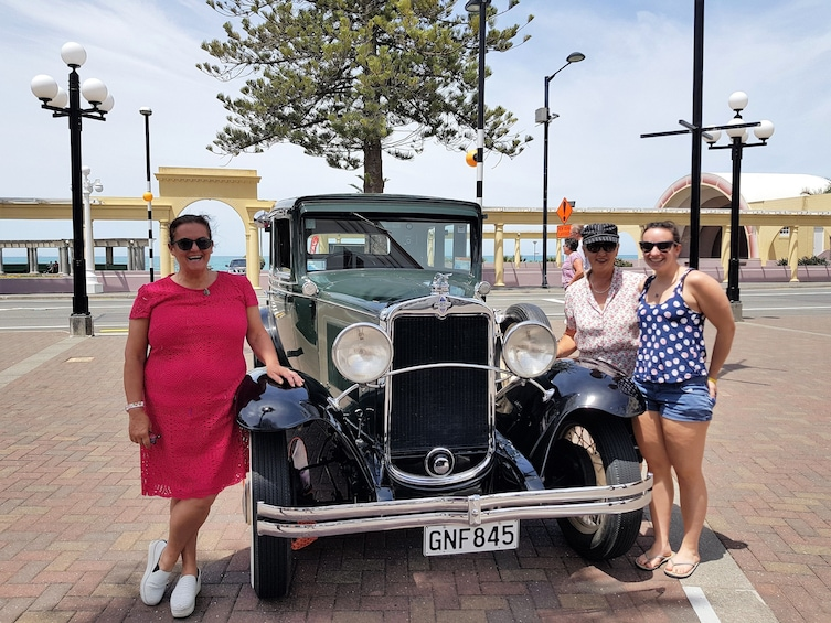 Show item 1 of 8. Women standing next to a vintage car in Napier