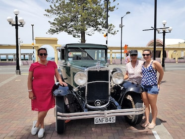 Women standing next to a vintage car in Napier