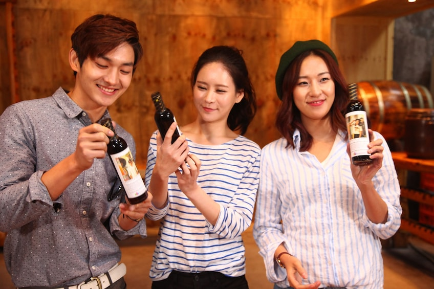 正在顯示第 4 張相片,共 10 張。 Three friends hold up bottles of beer in South Korea