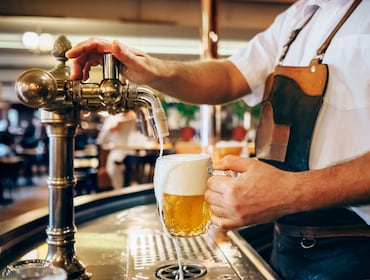 Bartender pouring a fresh beer at a local pub in Prague