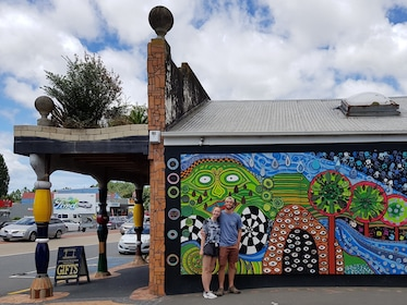 Couple poses in front of a restaurant mural