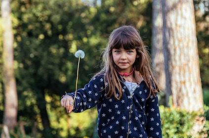 Young girl with a dandelion puff in a park in Florence