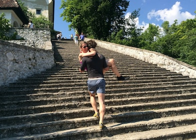 Man holding a woman and walking up stone steps at Lake Bled