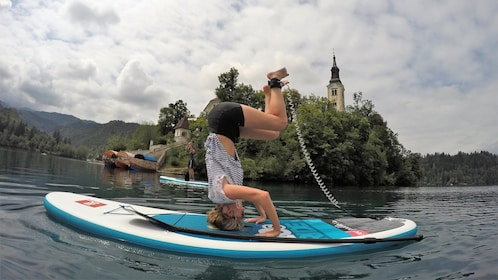 Person doing a handstand on a paddleboard at Lake Bled