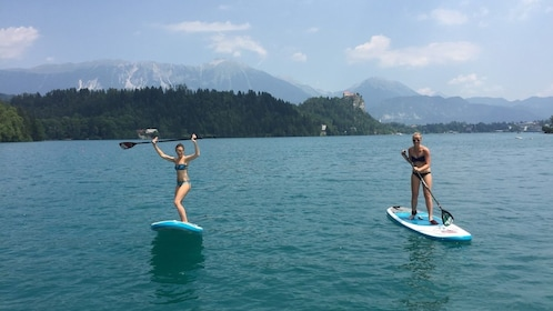 Two women on paddle boards at Lake Bled