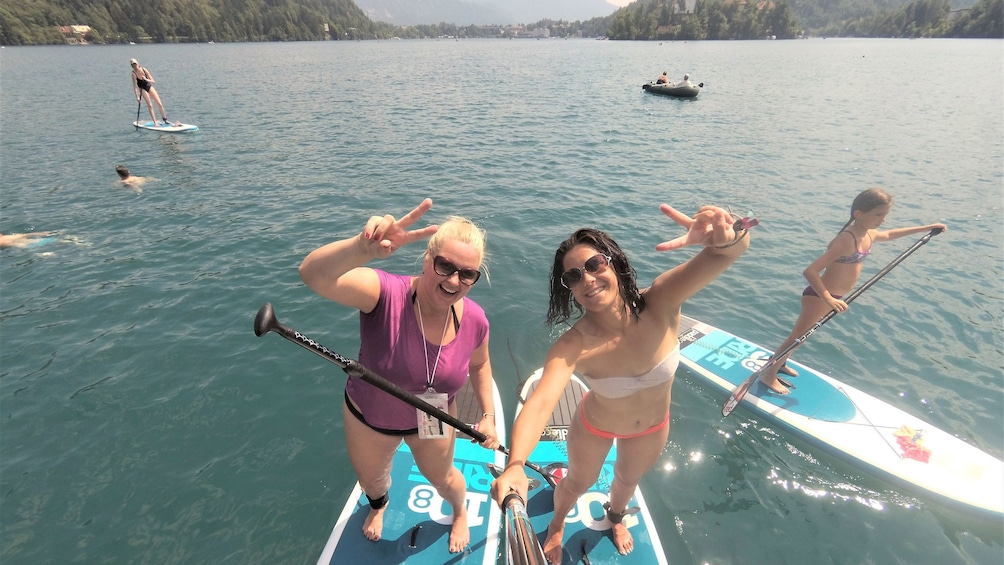 Show item 2 of 9. Ladies holding up peace signs while on a stand up paddle boarding activity in Lake Bled, Slovenia