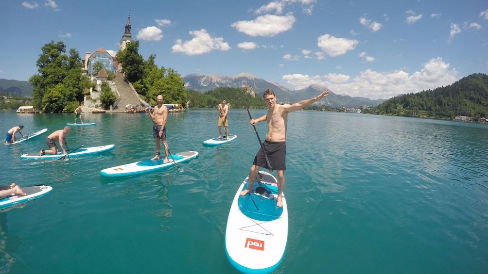 Show item 3 of 9. Group stand up paddle boarding in Lake Bled, Slovenia