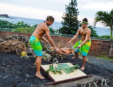 Two men put a pig underground to roast at a Luau.