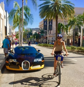 Woman riding a bike next to a Bugatti on the streets of West Hollywood