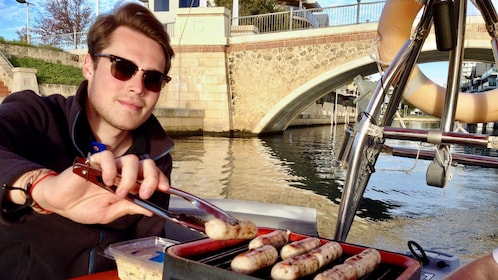 Man grilling sausages on a bbq boat in Australia