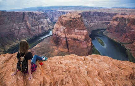 Woman sitting on the edge of the Grand Canyon at Horseshoe Bend