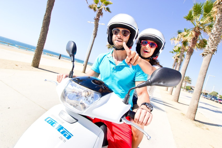 Ver elemento 5 de 5. Couple wearing sunglasses and helmets while riding a scooter in Menorca