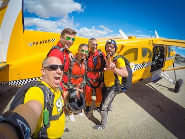 Skydiving group take selfie next to a plane