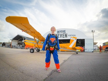 Skydiver in a Superman suit next to a Piper Cub