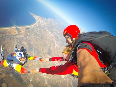 Skydivers hold hands during freefall