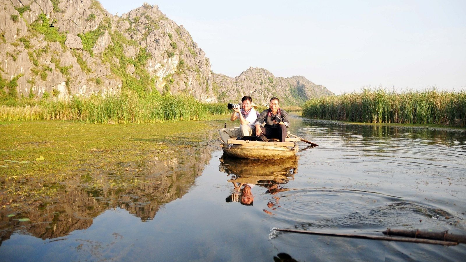 Men on a boat to Thung Nham bird park