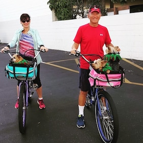 Couple each riding bikes, carrying one dog each in Carlsbad