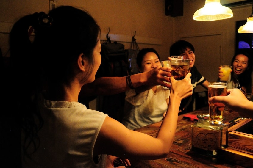 Show item 5 of 8. Group enjoying drinks at Golden Gai's cosy bars