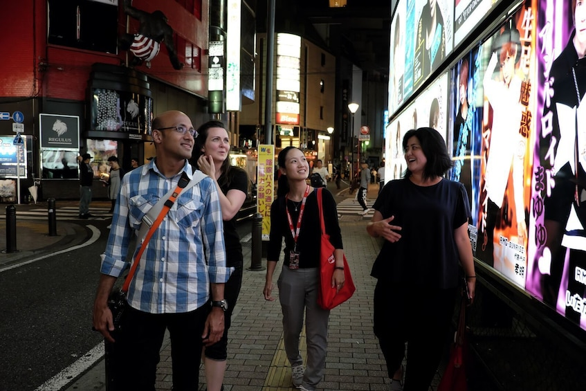 Show item 3 of 8. Group walking along the roads next to the bright billboards in Shinjuku
