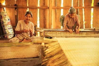 Two women weaving a bamboo tapestry in Vietnam