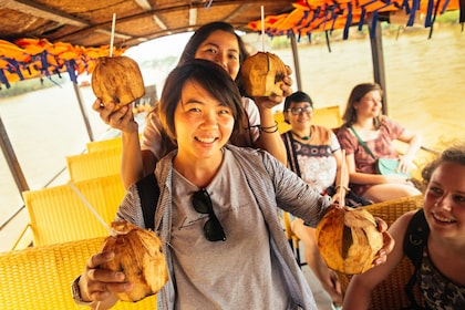 Tourist group holding coconut drinks on a tour boat in Vietnam