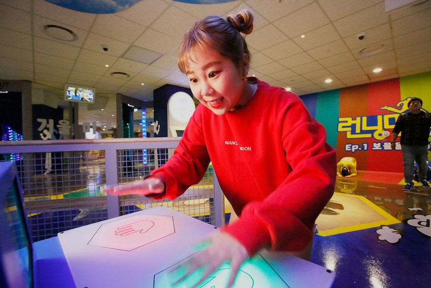 Carregar foto 5 de 10. Woman playing a game at the Running Man Thematic Experience Center