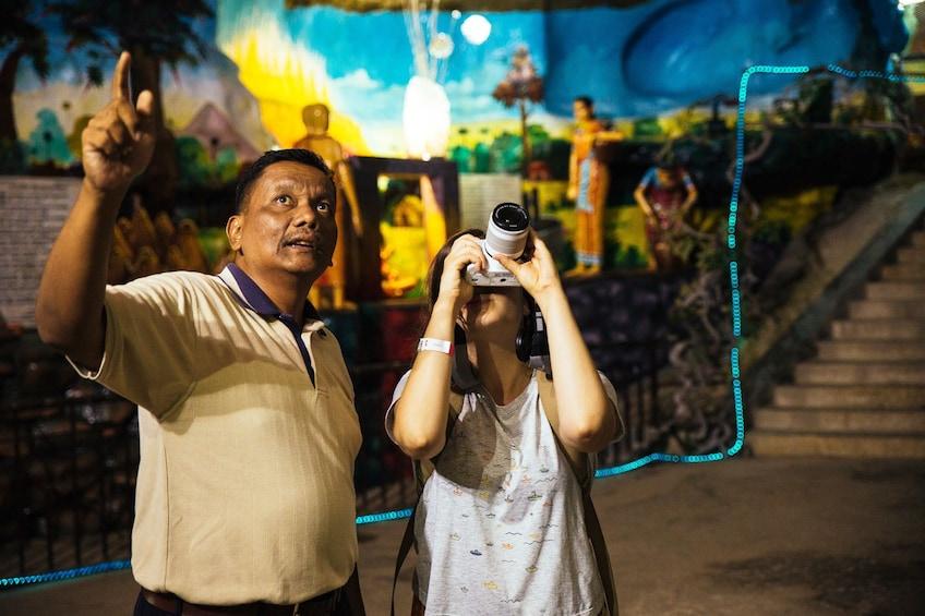 Show item 5 of 10. Tourists taking photos inside Batu Caves in Kuala Lumpur