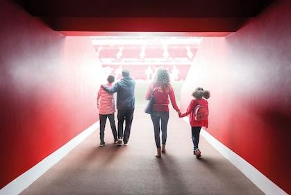 Couples walk through a tunnel at Liverpool Football Club stadium