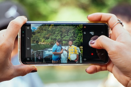 View of a phone taking a photo of a group at a waterfall in Taipei