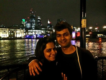 Couple poses next to the Thames at night