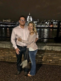 Two people pose in embrace next to the Thames at night