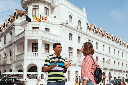 Tourist and guide standing in front of the Queen's Hotel in Kandy