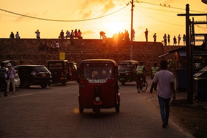 Tuk tuk vehicles on the road at sunset in Galle
