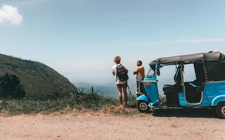Couple with Tuk tuk vehicle at a scenic viewpoint in the mountains of Sri Lanka