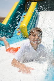 Child having fun on a water slide at the NEOSplash water park in Miami