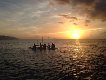 Group enjoying the sunset while stand up paddle boarding in Haleiwa