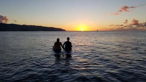 Couple enjoying views of the sunset while paddle boarding in Haleiwa