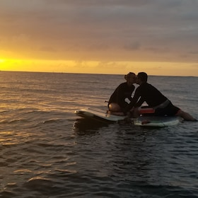 Couple kissing in the sunset while on stand up paddle boards in Haleiwa