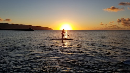 Woman paddle boarding during a sunset in Haleiwa