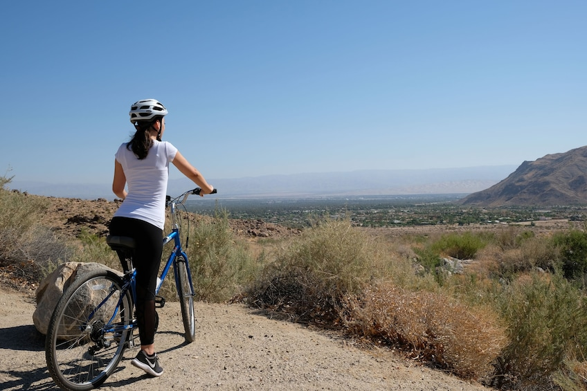 Show item 1 of 8. Woman enjoying scenic views of the city on a bike ride