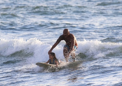 Man surfing with a child in Haleiwa