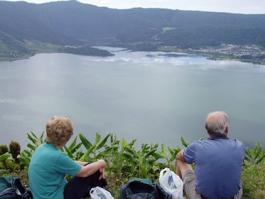 Couple sitting near a cliff enjoying a view of a lake on Sao Miguel Island