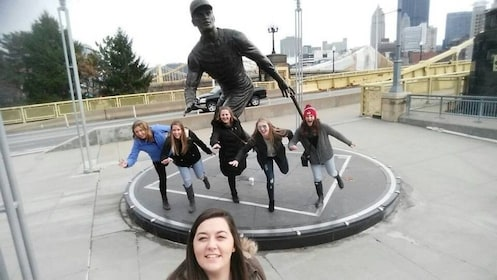 Group takes photo next to a statue of a person