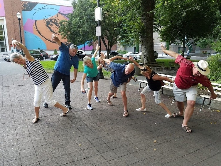 Show item 3 of 4. Group on a scavenger hunt posing in funny positions