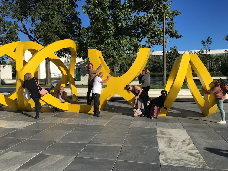 Show item 2 of 4. Tour group posing with sculpture on a scavenger hunt